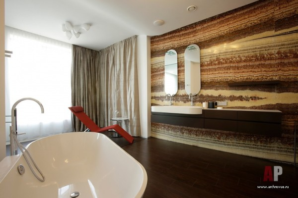 Стена ванной комнаты облицована ониксом