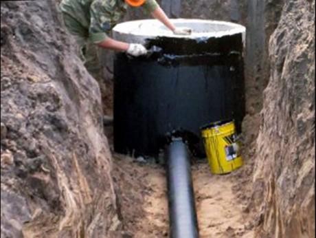 На фото – процесс гидроизоляции канализационного колодца