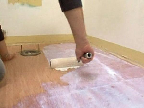 На фото – процесс грунтовки деревянного пола под линолеум