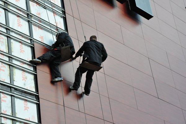 Работа монтажников на облицовке фасада