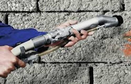 На фото показан процесс обрызга кирпичных стен