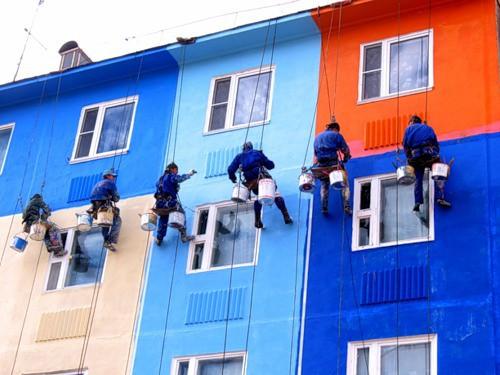 Процесс окраски фасада дома