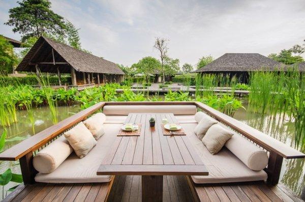 На фото, гостиная, имитирующая веранду на природе, с подобранными в тему фотообоями
