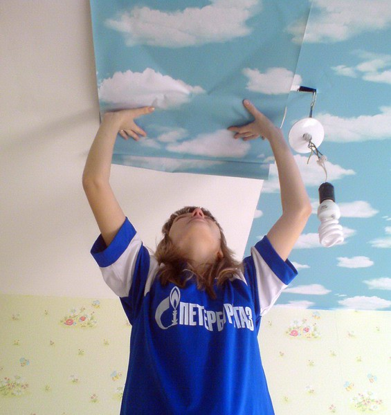 На фото, процесс оклейки потолка обоями