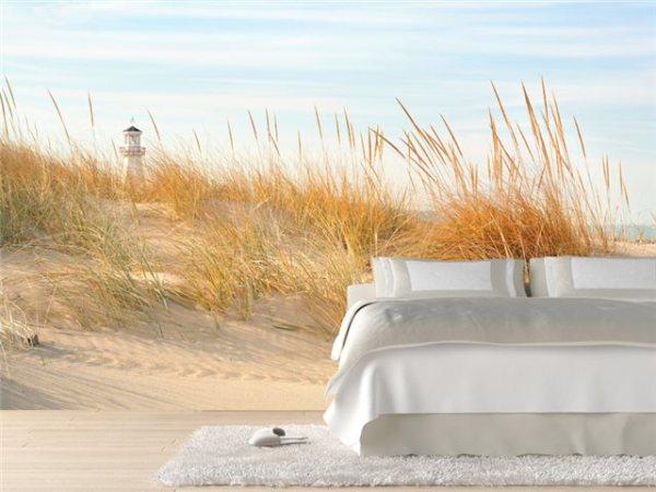 Песчаный морской берег с маяком вдалеке в интерьере спальни