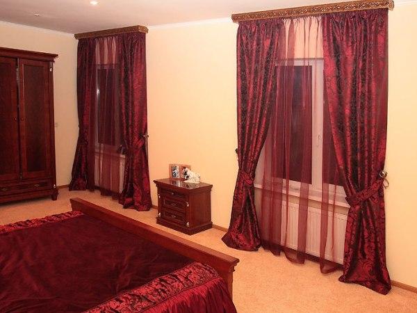 Красные шторы с однотонными обоями в интерьере спальни