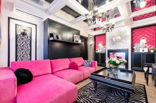 Розовая и чёрная мебель на фоне белых обоев с розовыми вставками