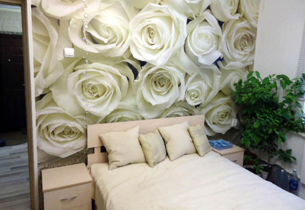 На фото, эффектные фотообои с множеством белых роз в интерьере спальни