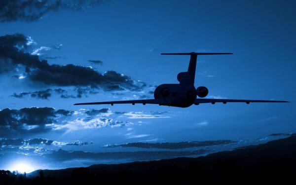 На фото, летящий самолёт на фоне восхода солнца
