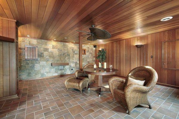 Гостиная в деревенском стиле, зашитая деревянной вагонкой, обработанной специальными пропитками, полностью изменившими цвет дерева