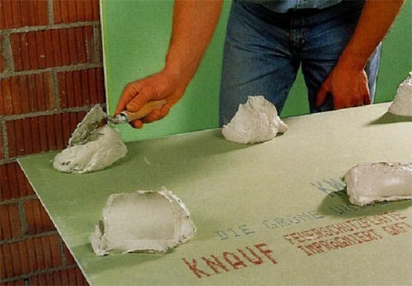 Нанесение клея на гипсокартон для обшивки кирпичной стены
