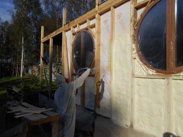 Нанесение жидкого пенного изолятора на стену дома. Средства индивидуальной защиты здесь просто необходимы