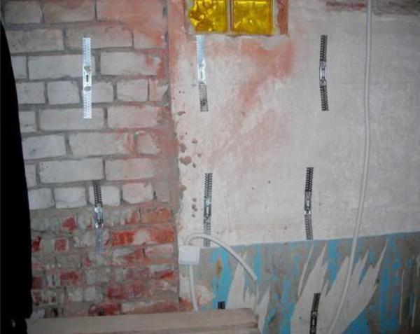 Стена, подготовленная к отделке, с закреплёнными оттяжками для установки металлических направляющих профилей