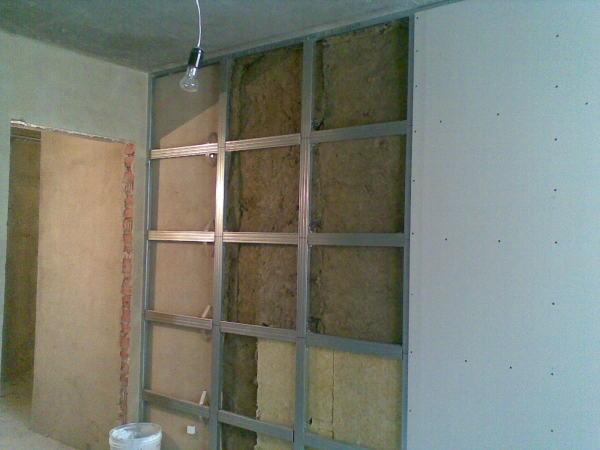 Каркас под обшивку стен гипсокартоном можно сооружать из различных материалов, чаще всего его делают из металлических профилей