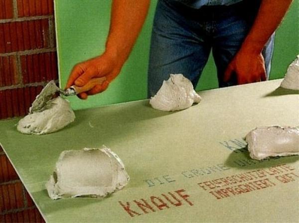 На фото показан пример, как наносится клей на лист гипсокартона, с последующим монтажом его на стену, который происходит сразу же после нанесения клея на лист