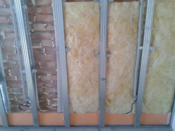 На фото показано утепление и обшивка кирпичной стены гипсокартоном с помощью сооружения металлического профиля