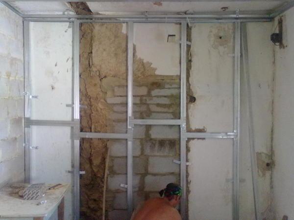 На фото представлен процесс монтирования металлического каркаса под обшивку стены гипсокартонными листами для её выравнивания