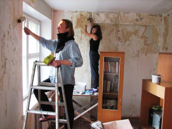 На фотографии показан процесс очистки стен и нанесение специального защитного состава дома своими руками
