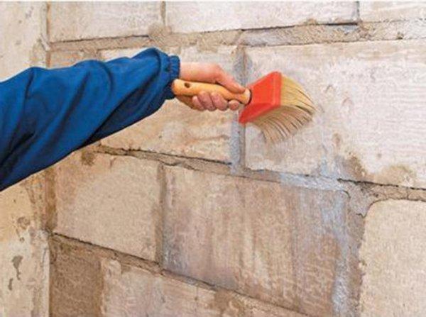 На фотографии показан процесс подготовки кирпичных стен специальным составом, перед оклейкой их гипсокартонными листами