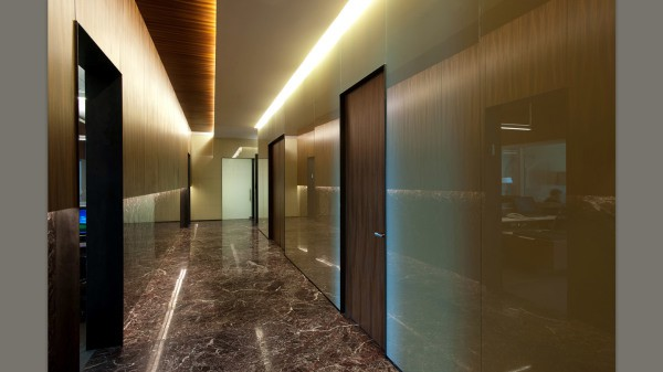 На фотографии представлен пример, как оформить стены коридора пластиковыми панелями, визуально расширив пространство с помощью глянцевой поверхности и подсветки