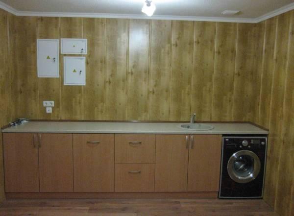 На фотографии представлен пример отделки стен кухни панелями мдф, что смотрится эстетично и довольно благородно, напоминая отделку деревом, но намного дешевле