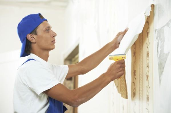 На фотографии представлен процесс очистки стен от старой отделки, обоев, которые довольно легко отходят от поверхности стен