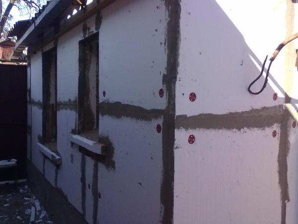 На фотографии вы видите пример обшивки старого кирпичного дома гипсокартонными листами с помощью пластиковых дюбелей