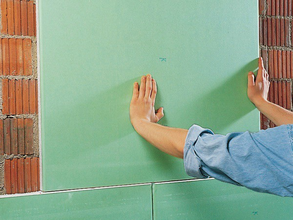 Наклеив лист гипсокартона на стену, его необходимо прижать и немного подержать, чтобы клей как можно крепче схватился с поверхностью