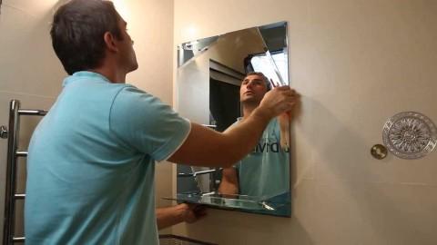 Мы видим процесс монтажа зеркала без рамы на стену ванной комнаты.