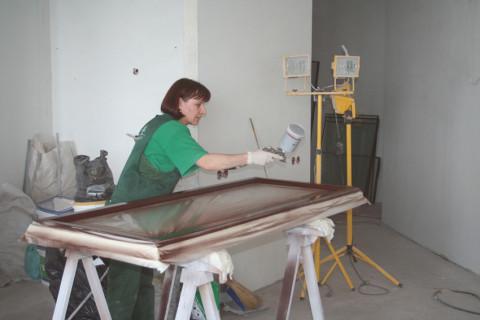 Мы видим процесс нанесения молотковой краски на металлическую дверь с помощью краскопульта