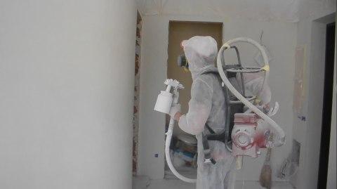 Мы видим процесс покраски стен с помощью компрессора на плечах.