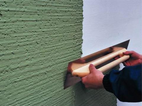 Мы видим процесс шпаклевания стены акриловой шпаклёвкой зелёного цвета