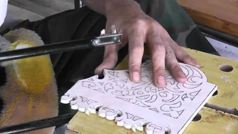 Мы видим процесс создания деревянного панно с помощью электролобзика