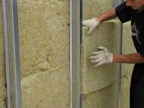 Мы видим процесс утепления стен дома с помощью ватного утеплителя