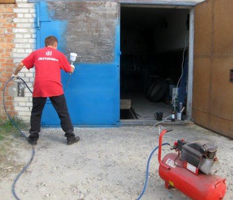 Процесс окрашивания металлических ворот нитро краской с помощью распылителя