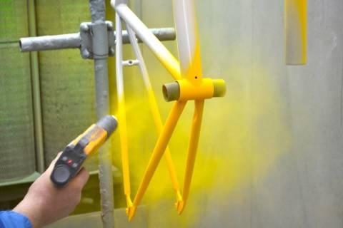 Распыление порошкового полимера на велосипедную раму.