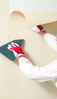 Резиновым шпателем полосу разравнивают и выжимают излишки клея из-под полотна