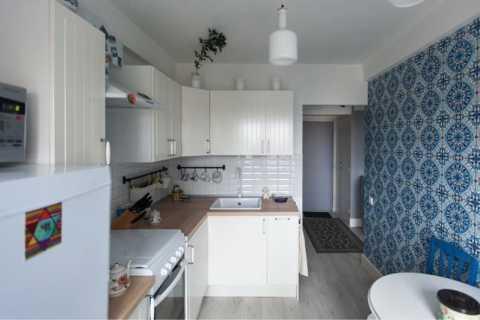 Белая кухня на фоне синих обоев