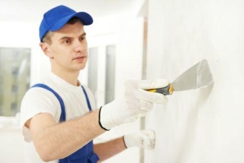 Очистка узким шпателем поверхности стены.