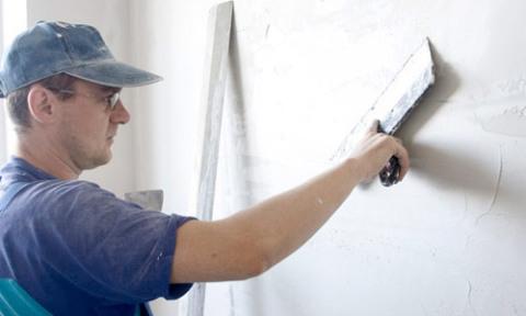 Применение широкого шпателя при шпаклевке стен.