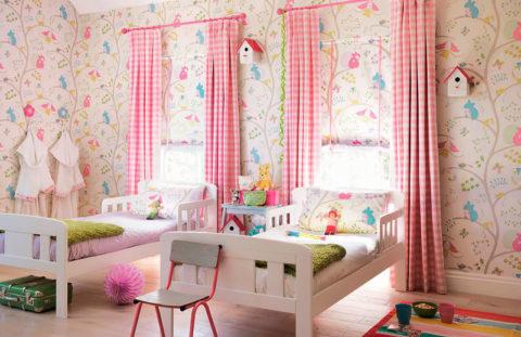 Симметричное расположение кроватей и штор на окнах уравновешивают свободный рисунок обоев