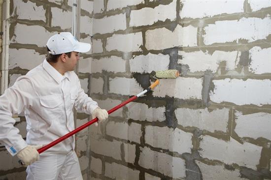 На фото – процесс грунтования пенобетонных стен