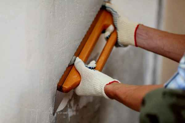 Процесс выравнивания стен перед нанесением на них настенных панелей из мдф