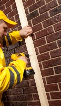 На фото мы видим процесс сооружения деревянного каркаса на кирпичной стене под гипсокартон