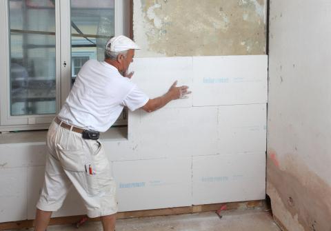 На фото мы видим процесс утепления внутренних стен дома с помощью листов пенопласта